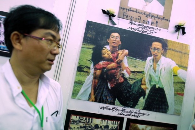 Win stands near famous historical picture taken in 1988, at the opening ceremony of memorial and exhibition marking the 25th anniversary of the democratic uprising, in Yangon