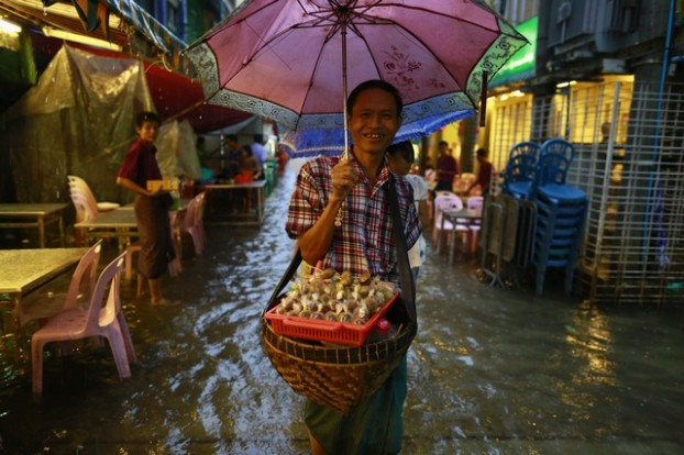 A man sells snacks along a flooded street during heavy rainfall in central Yangon
