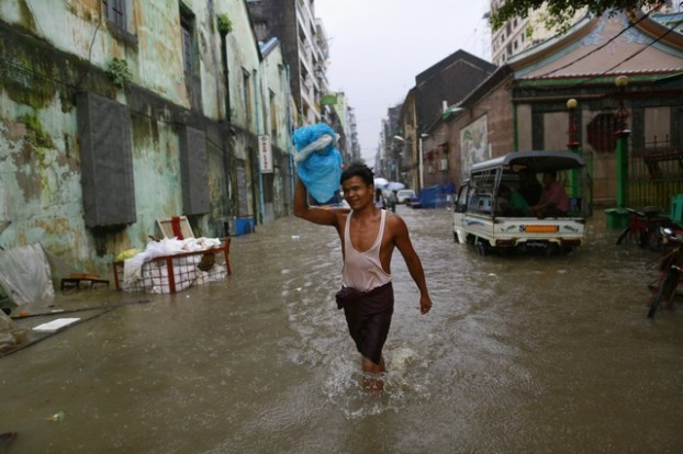 A man carries a bag as he walks along a flooded street during heavy rainfall in central Yangon