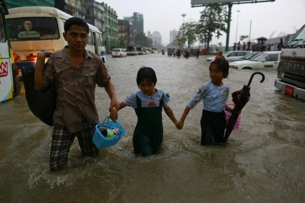 Schoolgirls walk with their father along a flooded street as they return from school, during heavy rainfall in central Yangon